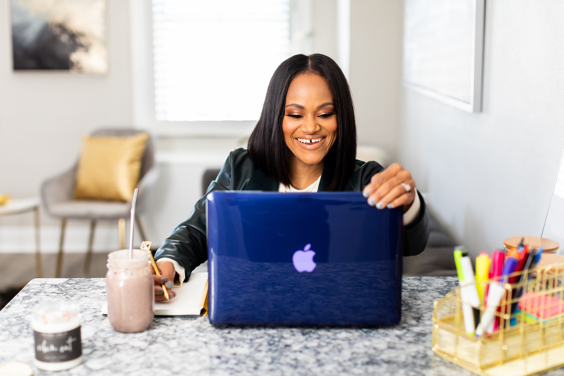 Qiana Solomon for The Virtual Key LLC, sitting at desk with MacBook and coffee helping entrepreneurs
