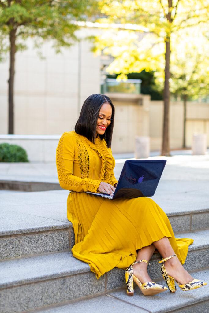 Qiana Solomon for The Virtual Key LLC sitting on concrete steps outside working on MacBook Pro